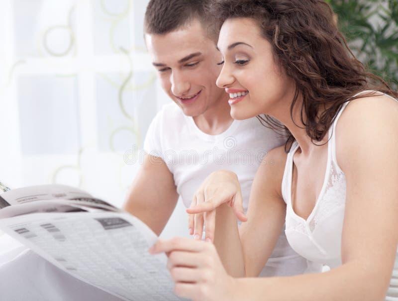 Ein junges Paar im Bett, das eine Zeitung liest lizenzfreie stockfotos