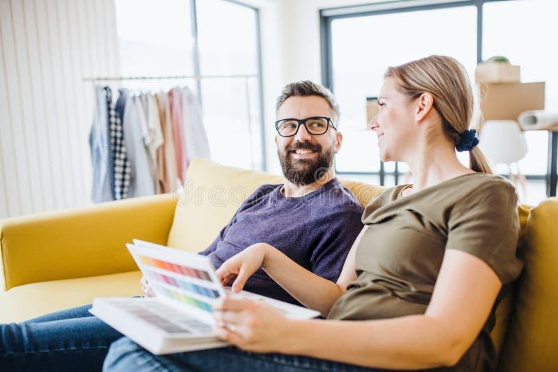 Ein junges Paar mit den Farbproben, die auf dem Sofa, bewegend in neues Haus sitzen stockfotografie