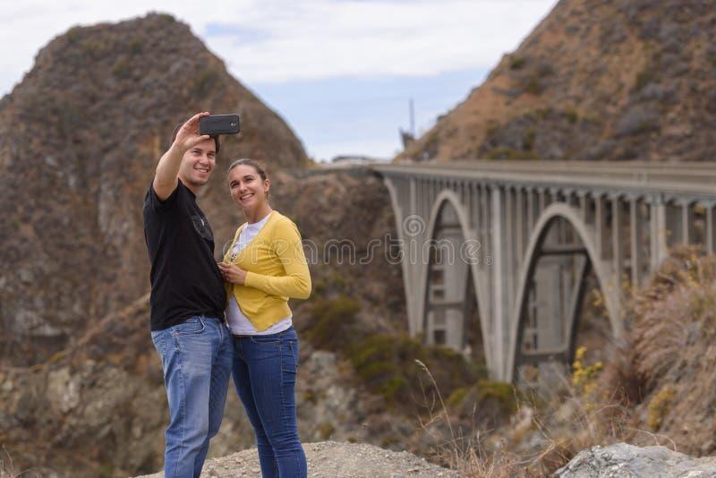 Ein junges Paar nehmen ein selfie im fron der großen Nebenfluss-Brücke, Big Sur, Kalifornien, USA lizenzfreie stockfotos