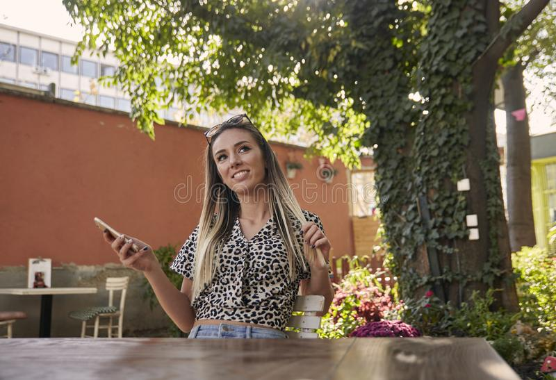 Ein junges schönes Mädchen, das draußen für ein Porträt, im Cafégarten, Smartphone halten aufwirft Sommertag, zufällige Kleidung stockbild