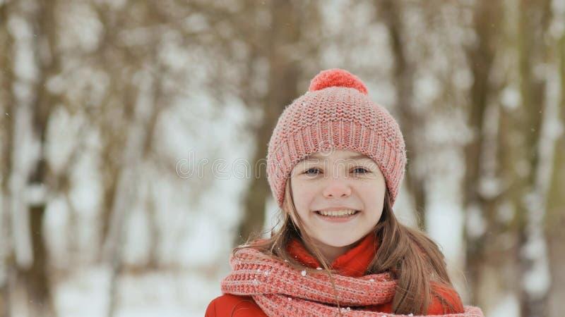 Ein junges Schulmädchen froh wirft einen Schneeball und bricht ihn mit einer Palme, wenn er fällt Gefühle der Freude Winterspaß h lizenzfreies stockbild