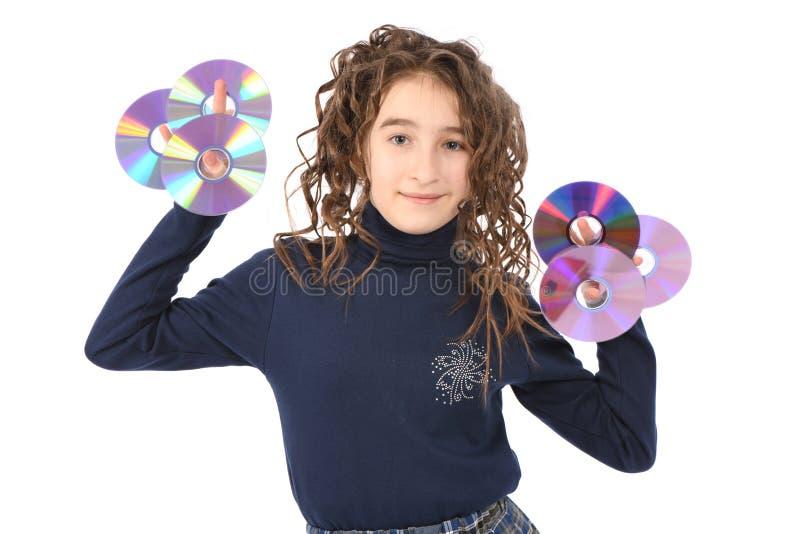 Ein junges Schulmädchen mit Lockenhaarholding CD oder dvd stockbild
