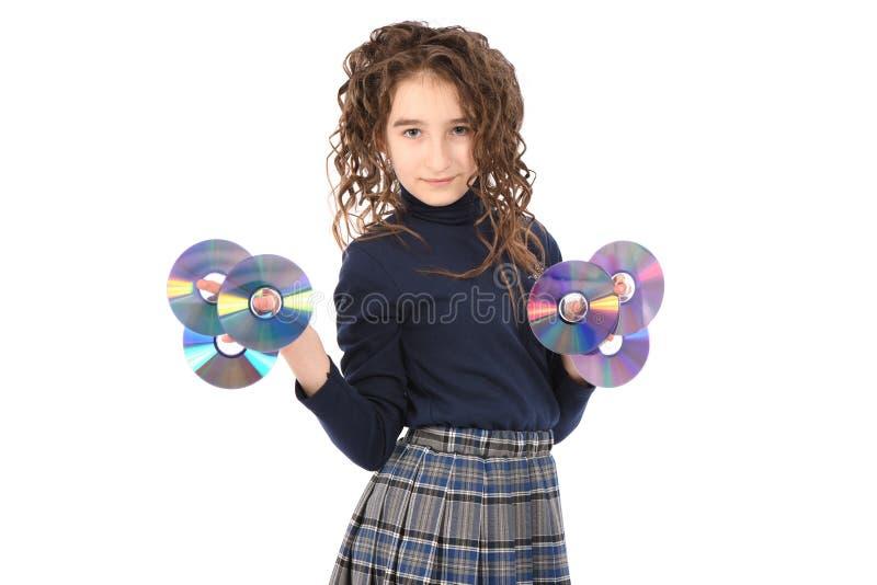 Ein junges Schulmädchen mit Lockenhaarholding CD oder dvd stockfotografie