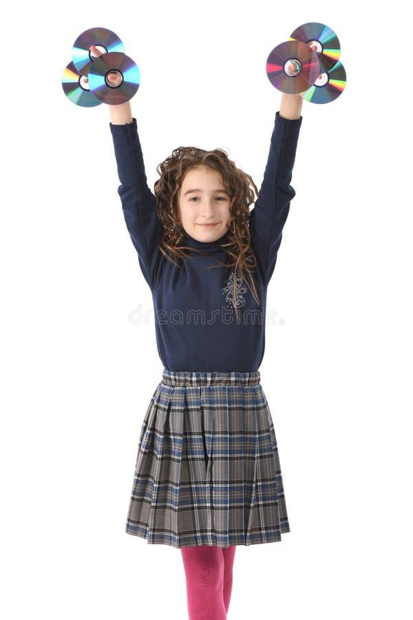 Ein junges Schulmädchen mit Lockenhaarholding CD oder dvd lizenzfreie stockbilder