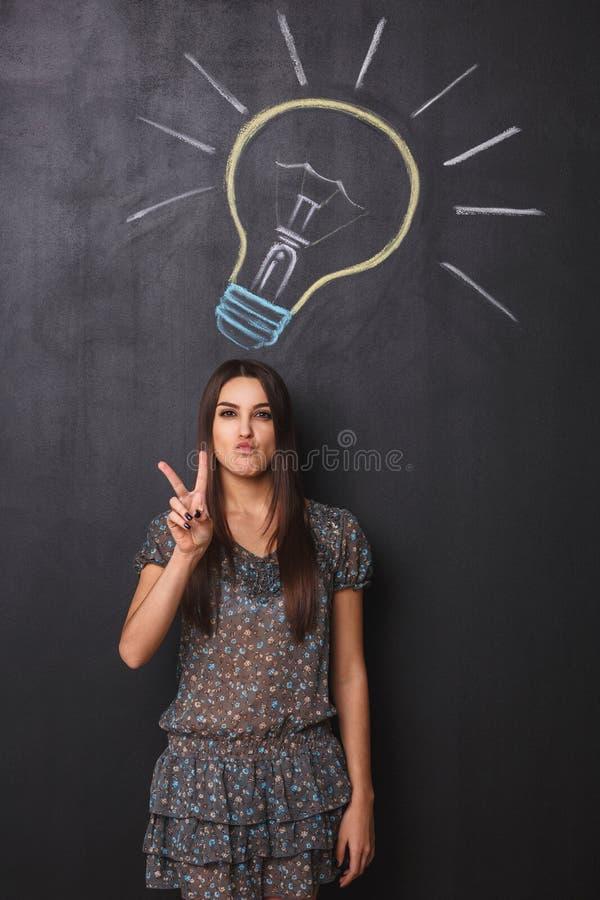 Ein junges Studentenmädchen mit Friedenszeichen hat eine großartige Idee auf der Tafel lizenzfreies stockbild