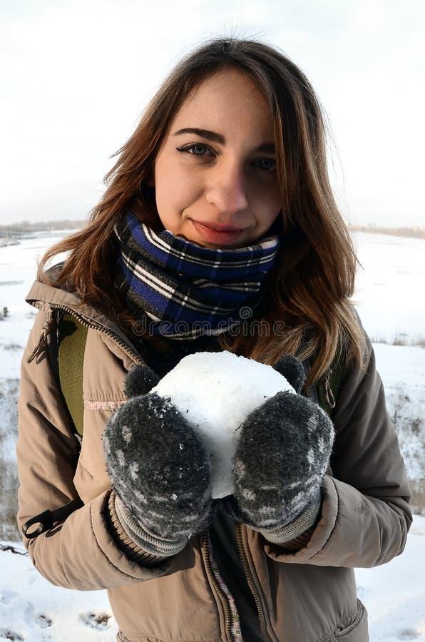 Ein junges und frohes kaukasisches Mädchen in einem braunen Mantel hält einen Schneeball vor einer Horizontlinie lizenzfreie stockfotografie