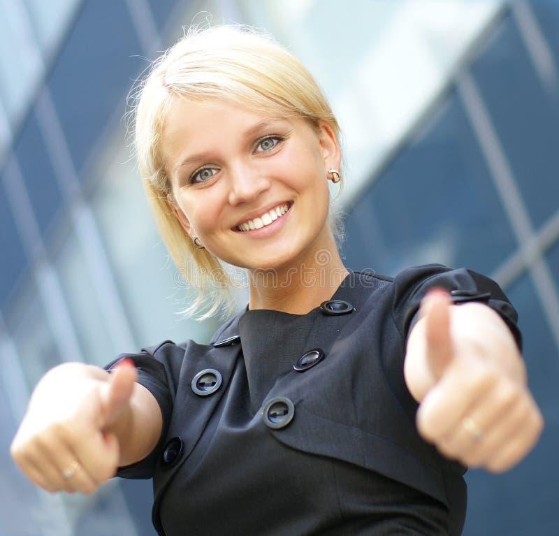 Ein junges und glückliches bloond ist Holdingdaumen oben lizenzfreie stockfotos