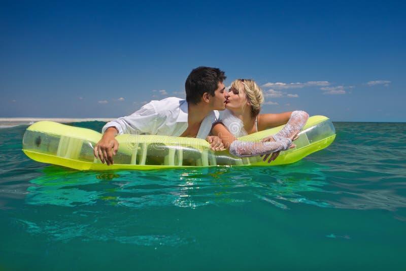 Neu-verheiratete Paare, die auf einer aufblasbaren Matratze genießen stockfoto