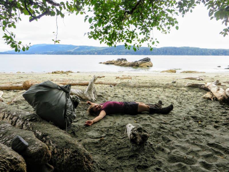 Ein junges weibliches Wandererlügen erschöpft auf dem Strand entlang der Westküstenspur, Vancouver Island, Britisch-Columbia, Kan lizenzfreie stockbilder