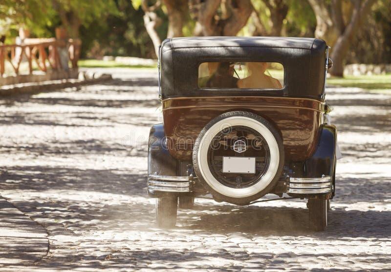Ein Jungvermähltenpaar fährt ein konvertierbares Retro- Auto stockfotografie
