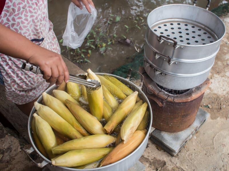 Ein Käuferzupacken ein Mais für ihren Kunden stockfoto