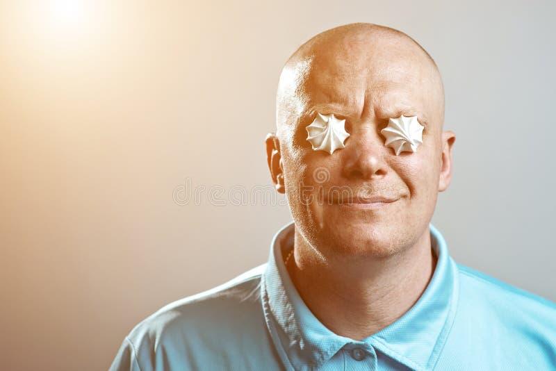 Ein kahler grober Mann in einem blauen Hemd setzte Meringen in seine Augen ein stockfotos