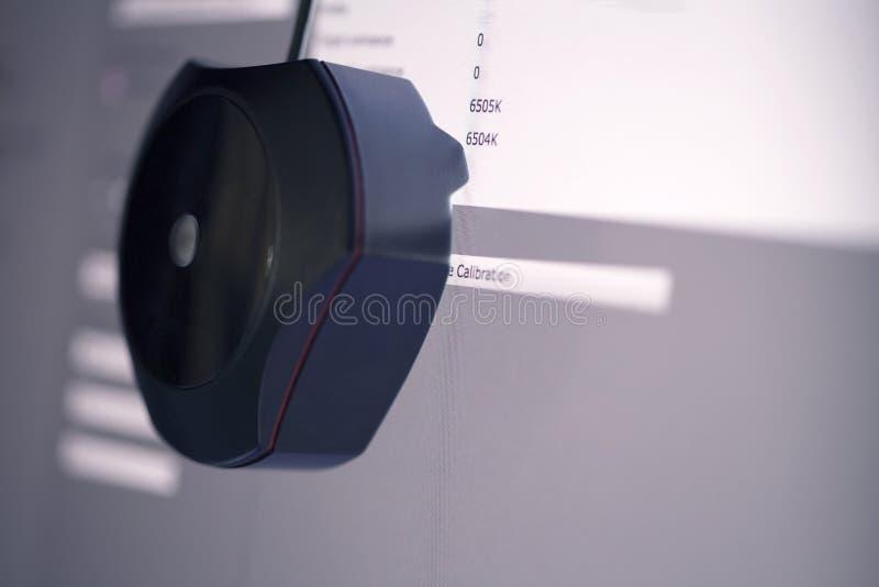 Ein Kalibrierer, der auf das Computermonitoranzeigefeld zu bigin Kalibrierung für Genauigkeitsfarbjob in Position bringt lizenzfreie stockfotos