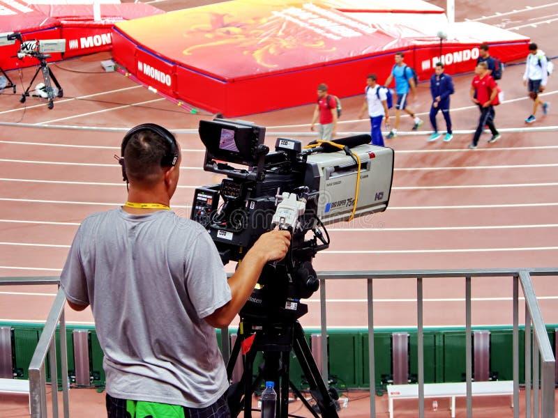 Ein Kameramann, der eine Filmkamera an der 2015 IAAF-Weltleichtathletik-Meisterschaft in Peking laufen lässt lizenzfreies stockbild