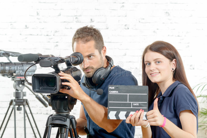 Ein Kameramann und eine junge Frau mit einer Filmkamera und -scharnierventil stockfotos