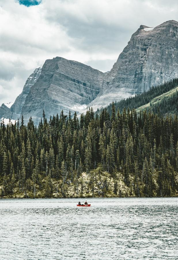 Ein Kanu auf maligne See im Sommer mit einem Hintergrund kanadischen Rocky Mountainss im Nationalpark des Jaspisses, Alberta, Kan lizenzfreie stockfotos
