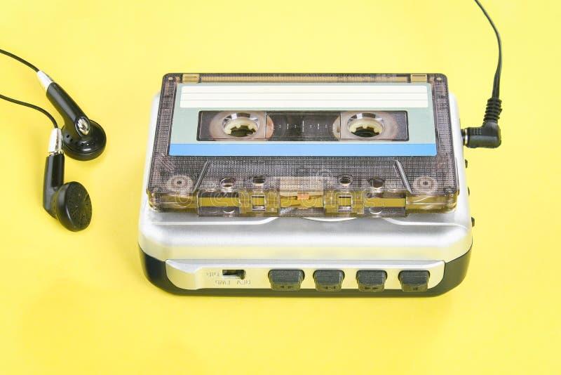 Ein Kassettenmusikspieler mit einer Kassette und Kopfhörern auf einem gelben Pastellhintergrund stockbilder