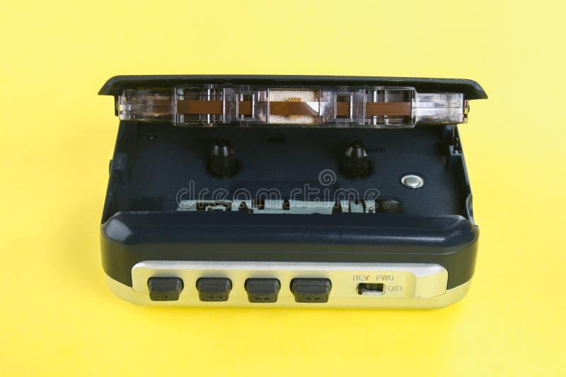 Ein Kassettenmusikspieler mit einer Kassette und Kopfhörern auf einem gelben Pastellhintergrund lizenzfreies stockfoto