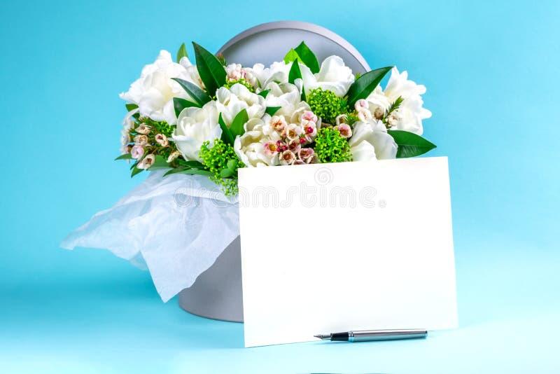 Ein Kasten mit weißen Tulpen und Zierpflanzen auf einem blauen Hintergrund Platz für Text lizenzfreies stockbild