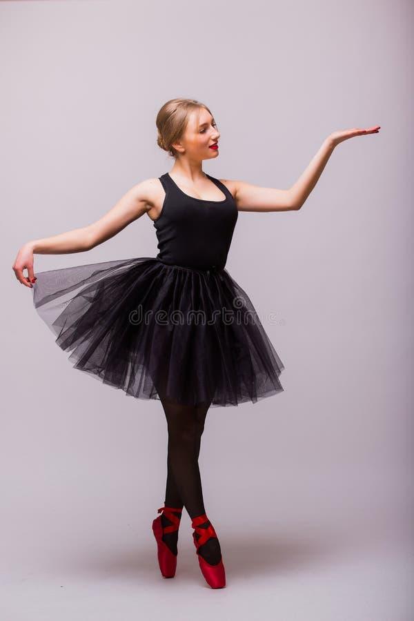 Ein kaukasisches Ballerina-Balletttänzertanzen der jungen Frau mit Ballettröckchen im Schattenbildstudio stockfotografie