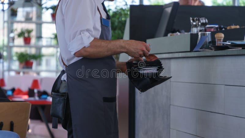 Ein Kellner in einem grauen Hemd mit dem Bargeld, das an steht, checkout stockfotos