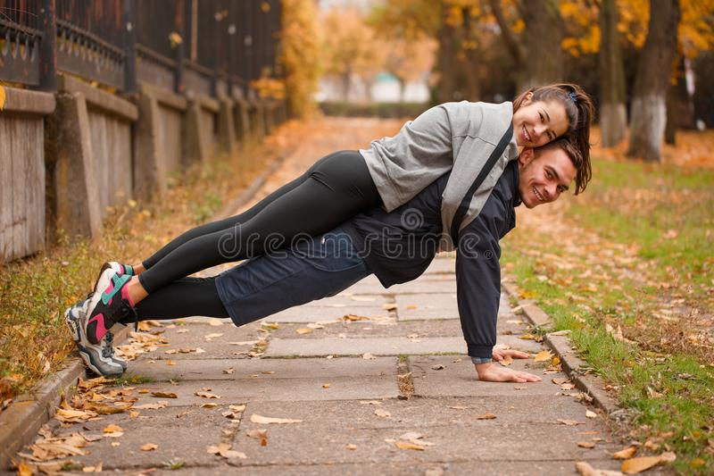 Ein Kerl drückt vom Boden mit einem Mädchen auf seinem zurück zusammen Draußen im Herbstpark stockbild