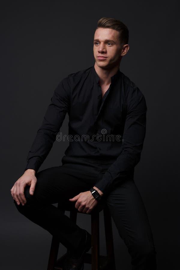 ein Kerl in einem schwarzen Hemd und in schwarzen Hosen sitzt auf einem dunklen Stuhl, auf einem grauen Hintergrund lizenzfreie stockfotos