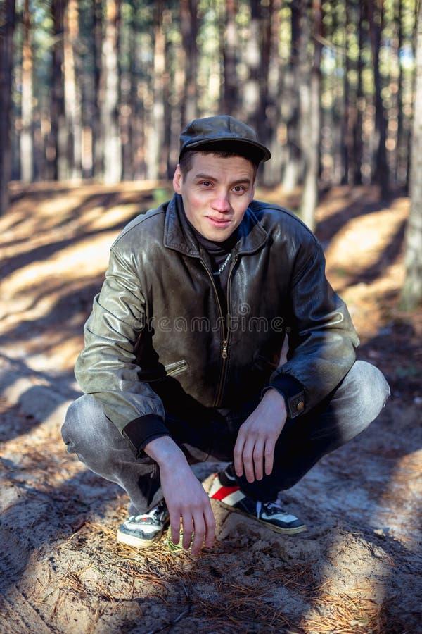 Ein Kerl in einer Lederjacke und in einer Kappe sitzt auf einer Straße in einem Wald stockfotografie