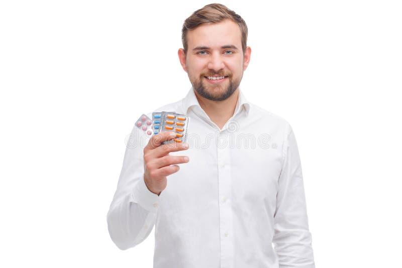 Ein Kerl halten eine Platte mit Pillen auf einem Weiß lokalisierten Hintergrund stockbild