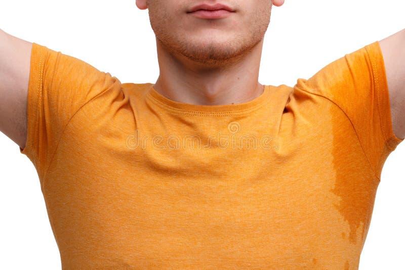 Ein Kerl kleidete in einem T-Shirt, angehobene Hände mit den nassen verschwitzten Achselhöhlen an Nahaufnahme Lokalisiert auf Wei lizenzfreies stockfoto