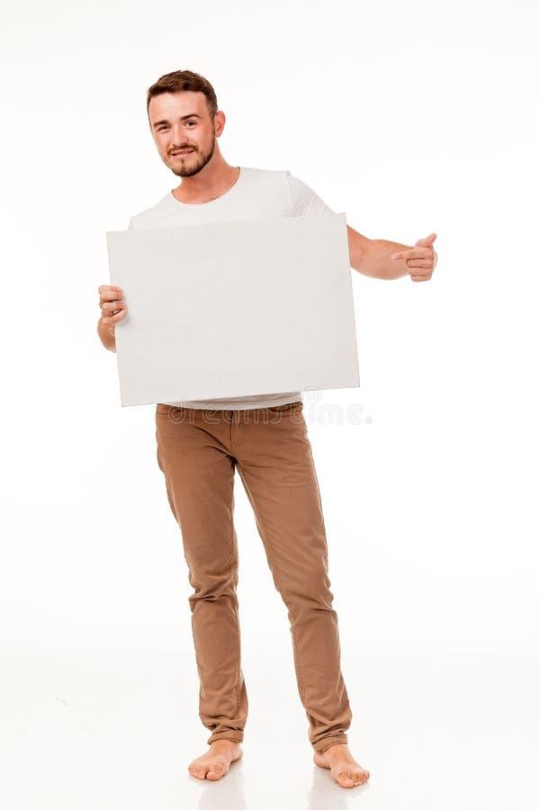 Ein Kerl mit einem Bart, der mit einem weißen Zeichen aufwirft Für die Werbung, können das Logo und die Visitenkarten, die Kontak lizenzfreie stockfotografie