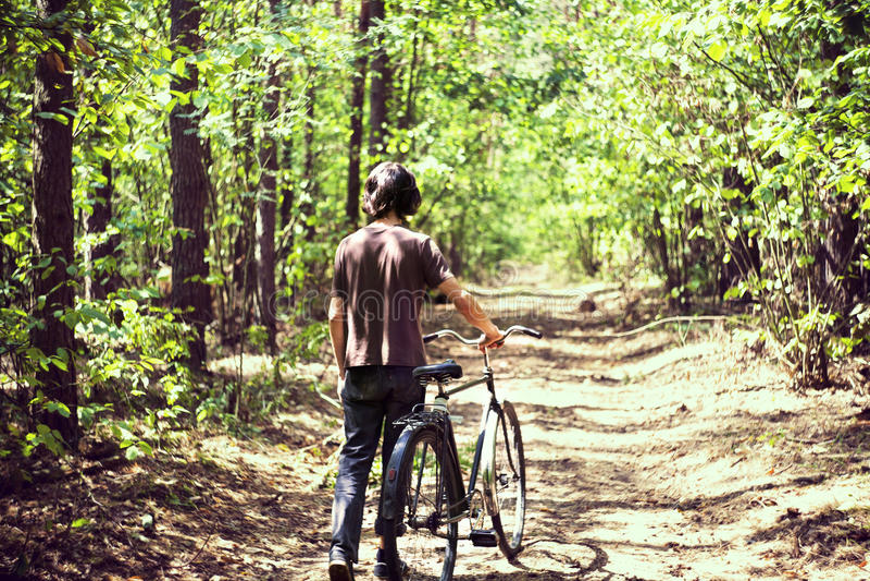 Ein Kerl mit einem Fahrrad im Waldsommerwald, in den grünen Blättern, in den grünen Bäumen und im Gras Alte Schulfahrrad lizenzfreie stockbilder