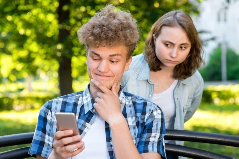 Ein Kerl mit einem Mädchen im Sommer in der Natur Ein junger Mann, der das Telefon liest eine Korrespondenz untersucht Die Mädche stockfoto