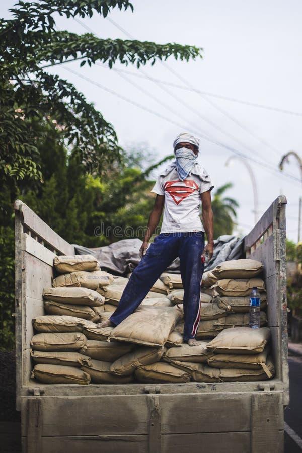 Ein Kerl mit einem Supermannhemd wirft auf einem Stapel von cementbags auf stockfotos