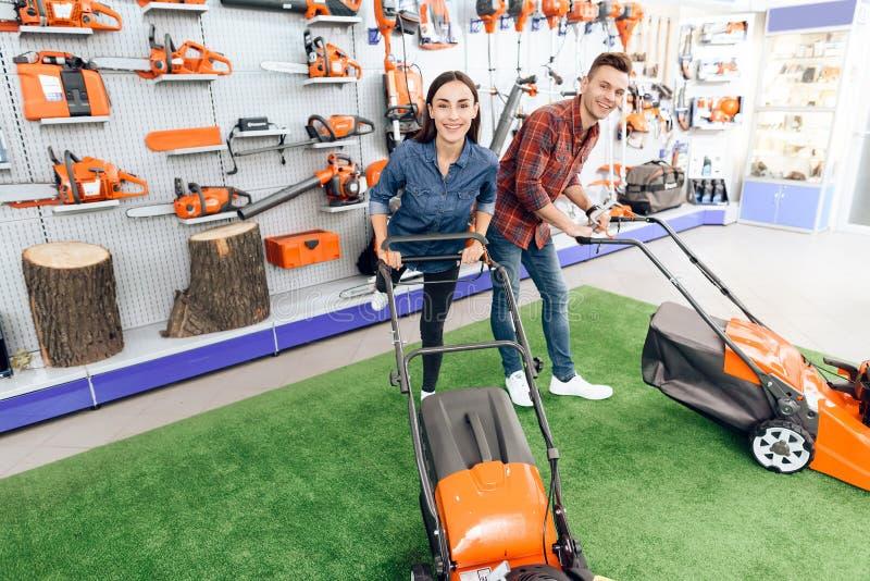 Ein Kerl und ein Mädchen werfen auf der Kamera mit einem Rasenmäher auf lizenzfreie stockfotografie