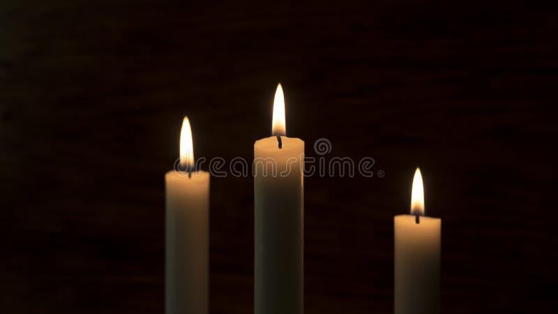 Ein Kerzenfeuer Drei Kerzen auf einem dunklen Hintergrund stockbilder