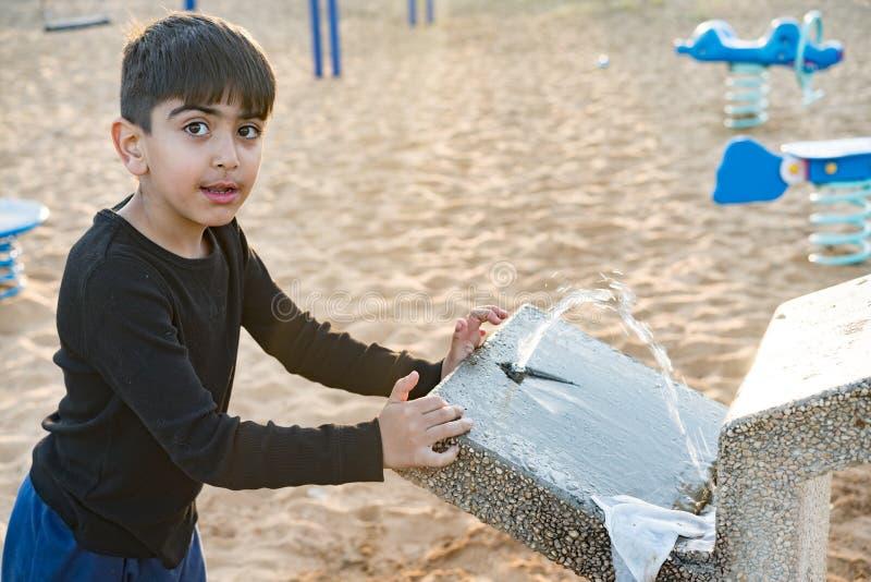 Ein Kind benutzt einen Schmutzwasserhahn lizenzfreie stockbilder