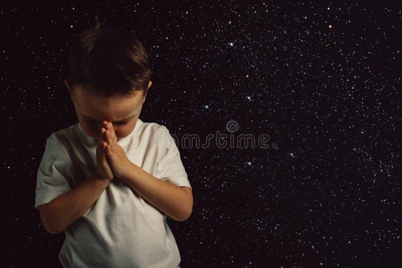 Ein Kind beten zu den Gotterr?tenh?nden lizenzfreie stockfotografie