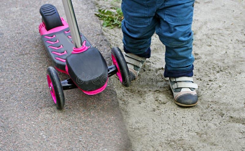 Ein Kind, das einen Trittroller reitet lizenzfreie stockfotos
