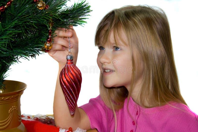Ein Kind, das einen Weihnachtsbaum verziert. lizenzfreie stockfotografie