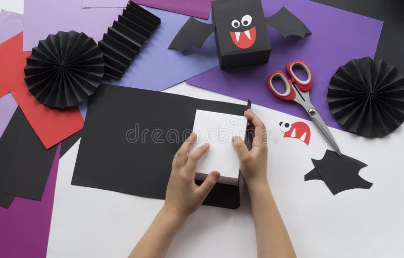Ein Kind, das Halloween-Dekorationen von farbigem Papier macht lizenzfreie stockbilder