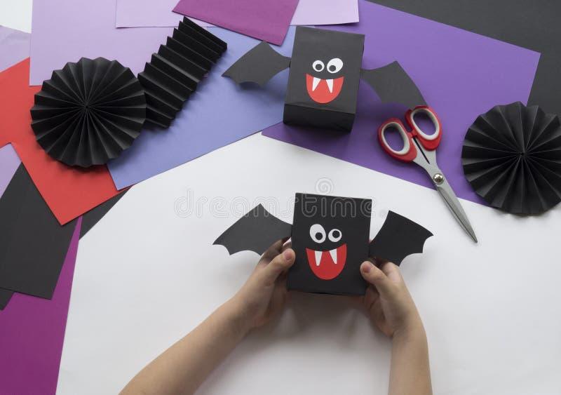 Ein Kind, das Halloween-Dekorationen von farbigem Papier macht stockfotos