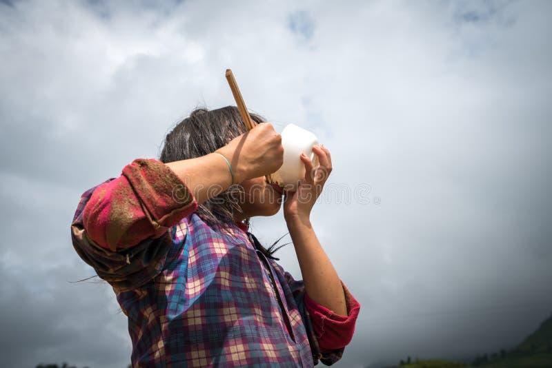 Ein Kind, das mit Schüssel und Essstäbchen auf Reisfeld in Asien zu Mittag isst Konzept der Armut, Lebensmittelknappheit, Kinder  lizenzfreie stockfotografie