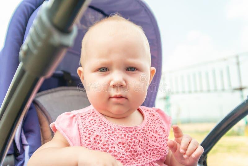 Ein Kind in einem Kinderwagen draußen im Park, ein kleines Mädchen untersucht die Kamera stockbild