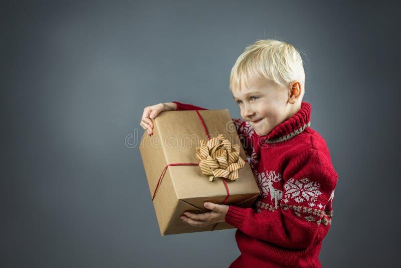 Ein Kind in einem Weihnachtspulli hat ein handwerkliches Geschenk stockbilder