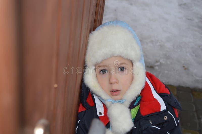 Ein Kind in einem Winterhut mit einem erschrockenen Blick stockfoto