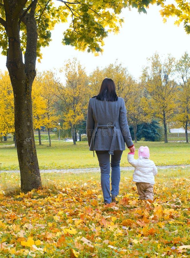 Ein Kind im Herbst auf der Natur und der Mutter stockbild