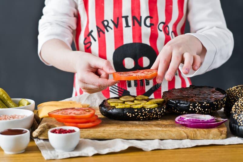 Ein Kind im Schutzblech eines Chefs bereitet einen Burger in der Küche zu Rezept für das Kochen des schwarzen cheeseberger Selbst stockfoto