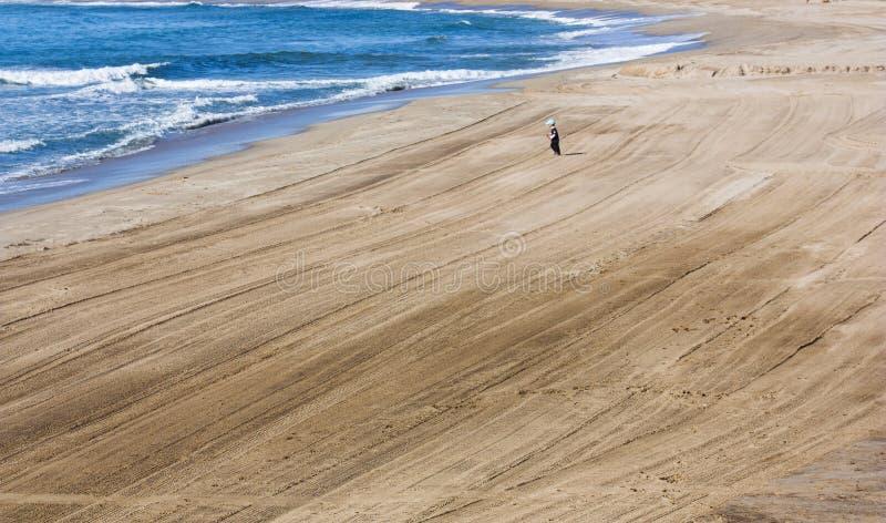 Ein Kind läuft entlang einen leeren Strand vom Meer Spanien Tarragona stockfotografie