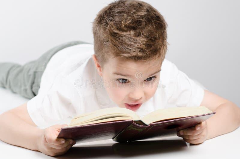 Ein Kind liest ein Buchlügen stockbilder